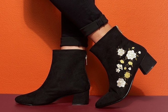 Feet sporting a pair of black cloth boots (one with flowers embroidered on the outside)