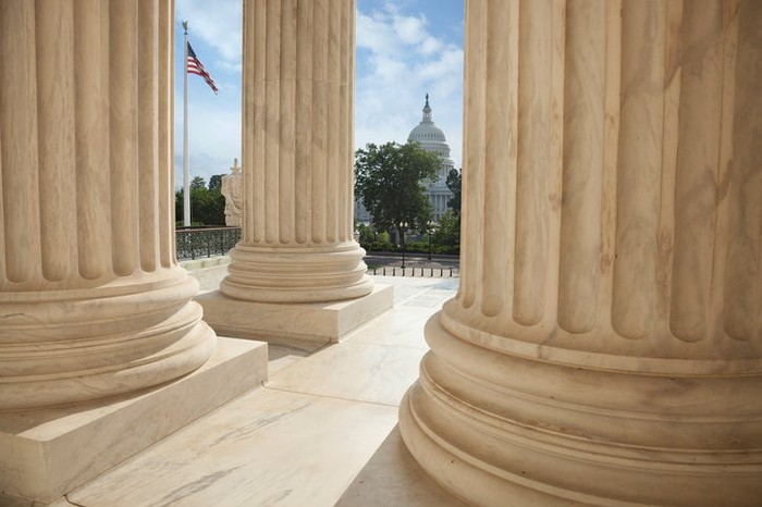 Marble columns and the U.S. Capitol Building in the background.
