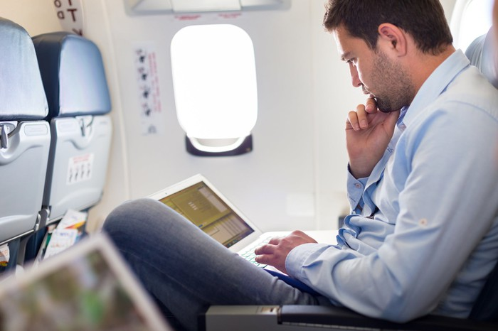 A man working on a laptop on a plane
