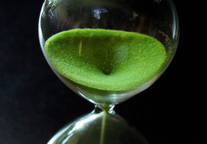 close-up of hourglass, with green sandy substance slipping through it