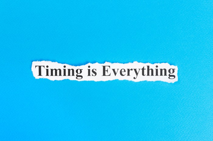 timing is everything, printed on a torn piece of paper laid against a blue background