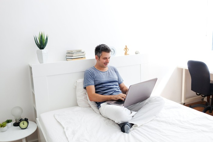 Man sitting in bed while working on a laptop in bed