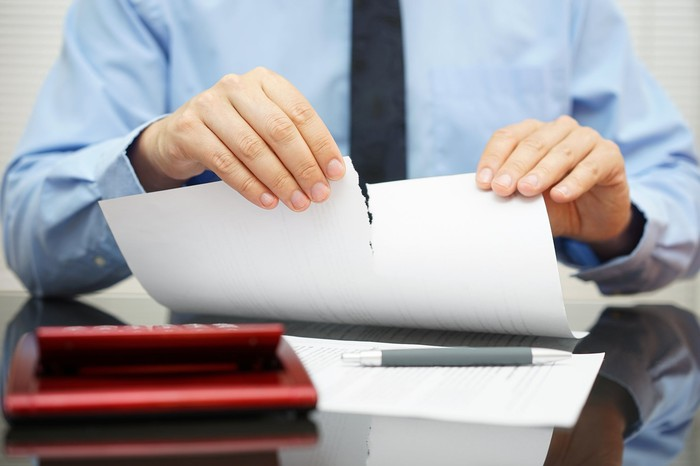 person sitting at desk and tearing a sheet of  paper