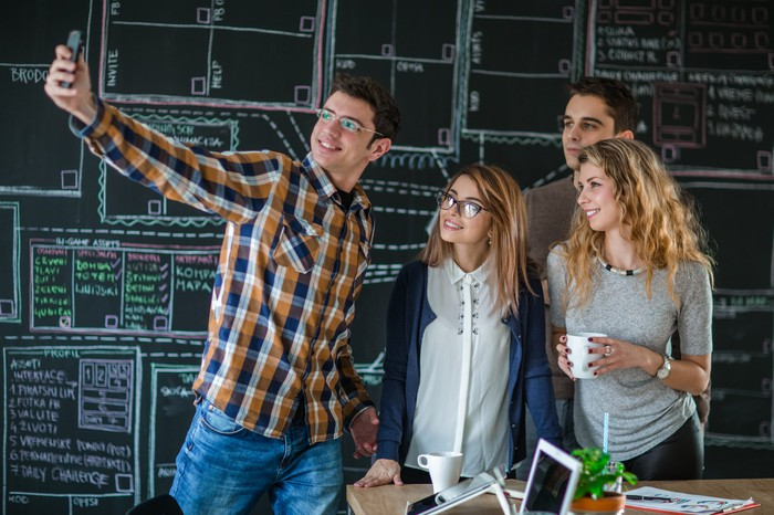 Young adults taking a selfie in front of a blackboard