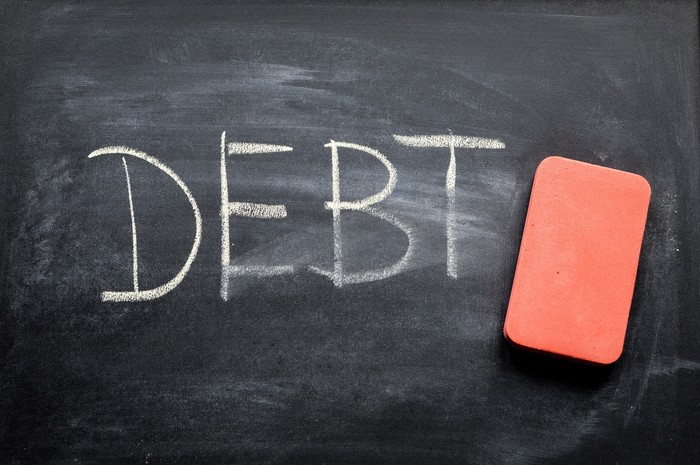 """Blackboard with a red eraser on it. """"DEBT"""" is written in white letters and has been partially erased."""