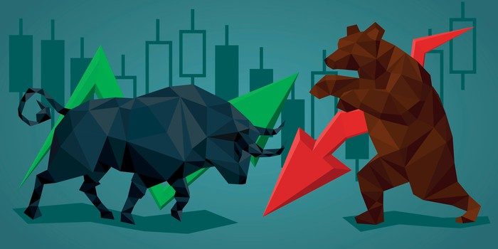 Bull and a bear appearing to fight each other, with a green arrow pointing up and a red arrow pointing down coming from opposing sides of the picture.