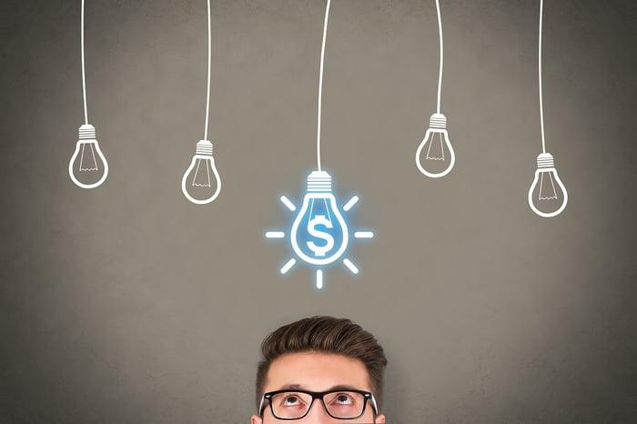 Man with eyeglasses looks up at lightbulbs drawn on chalkboard.
