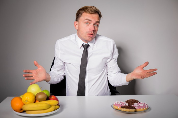 Man in white shirt shrugging over his dining choices -- a plate with four donuts or one with fresh fruits piled up
