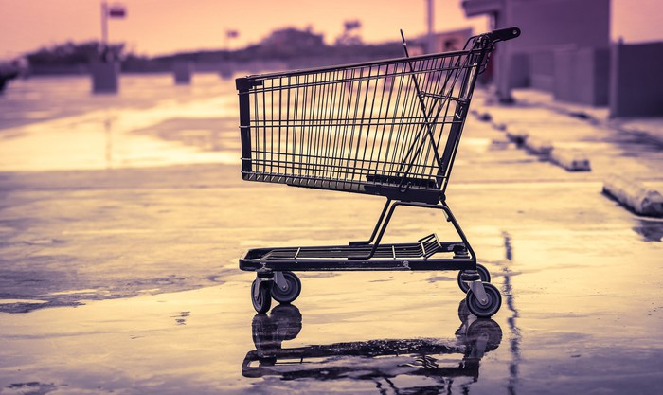 An empty shopping cart in an empty store parking lot