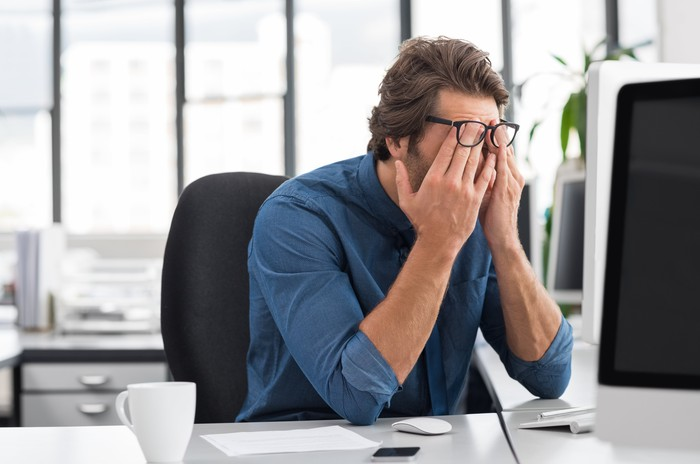 A person rubbing their eyes after looking at a desktop computer.