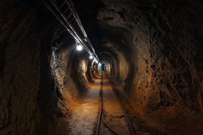 An underground mine passage with rails and lights.