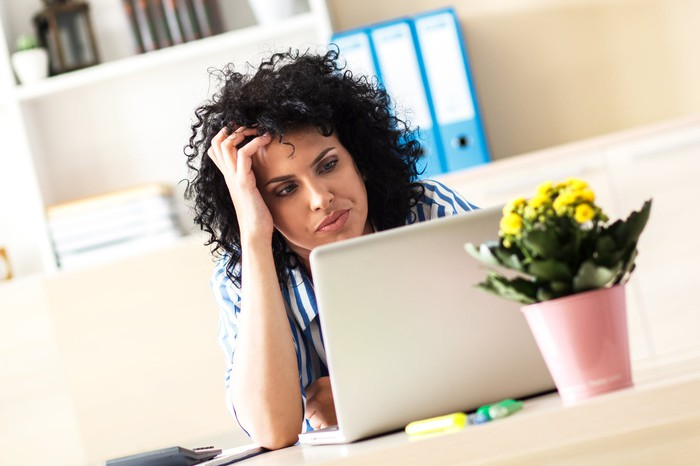 A frustrated women holding her hand to her head while reading an article on her laptop.