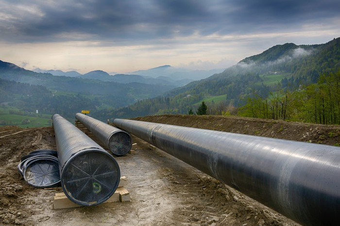 A pipeline under construction with dark clouds on the horizon.