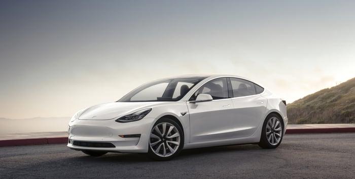 A white Tesla Model 3, a compact luxury sedan.