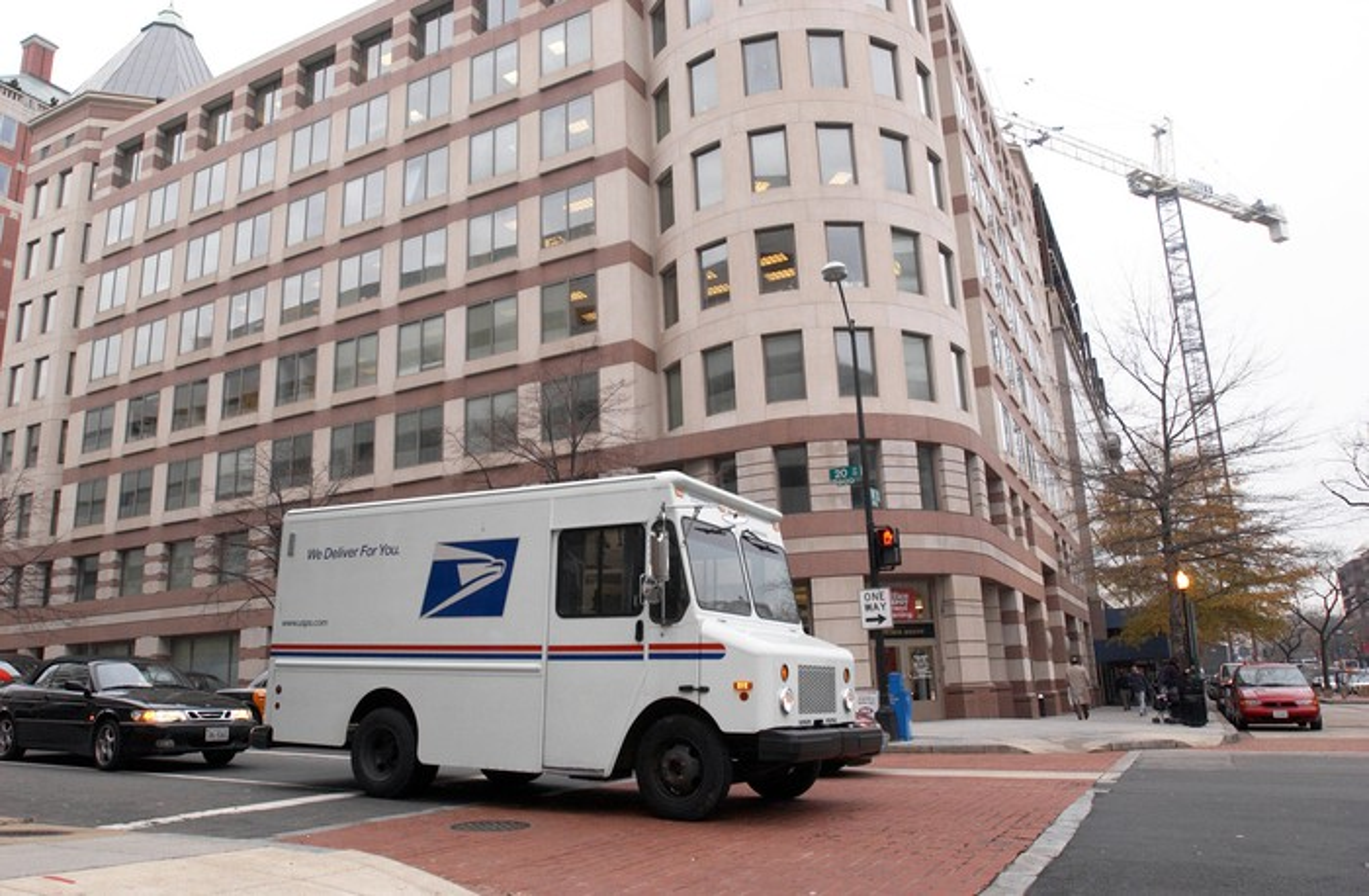 A U.S. Postal service truck driving down a city street.