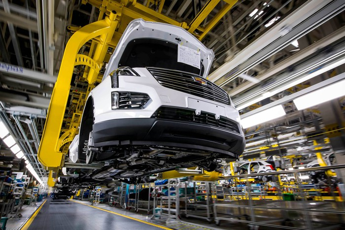 A partially assembled Cadillac XT5 SUV is shown on a factory assembly line.