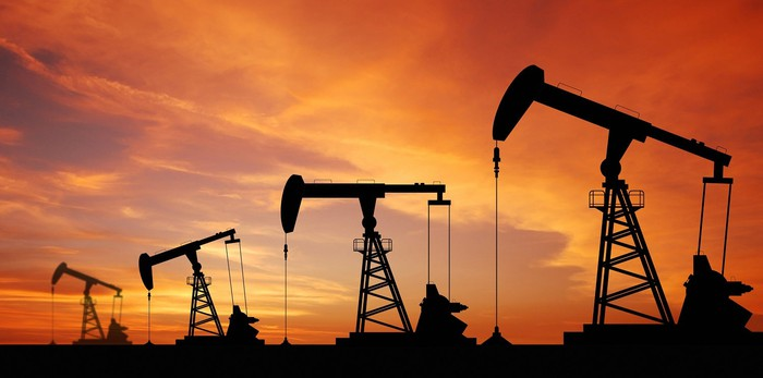 Four oil pumpjacks in operation at sunset