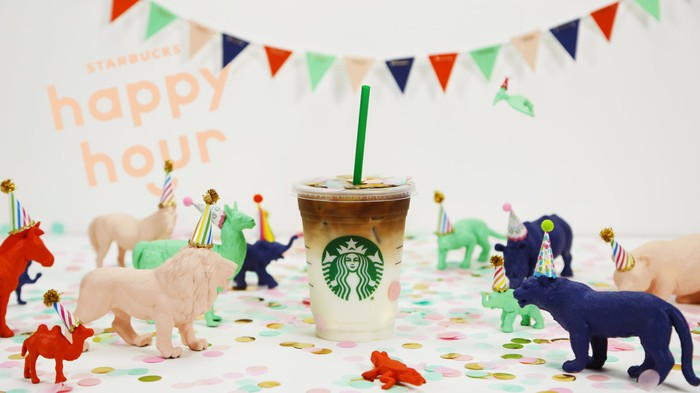 A Starbucks beverage surrounded by toy aniamls in party hats.