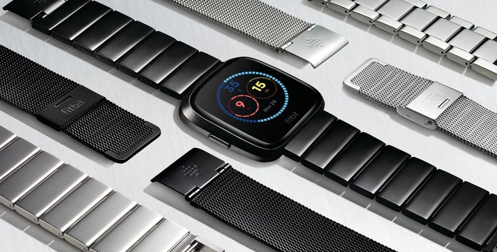 Fitbit Versa laying on a table with band accessories