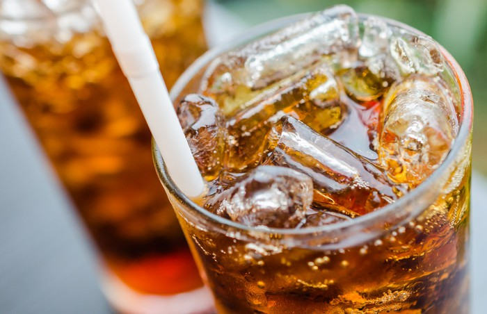 Brown soda and ice in a glass with a straw.