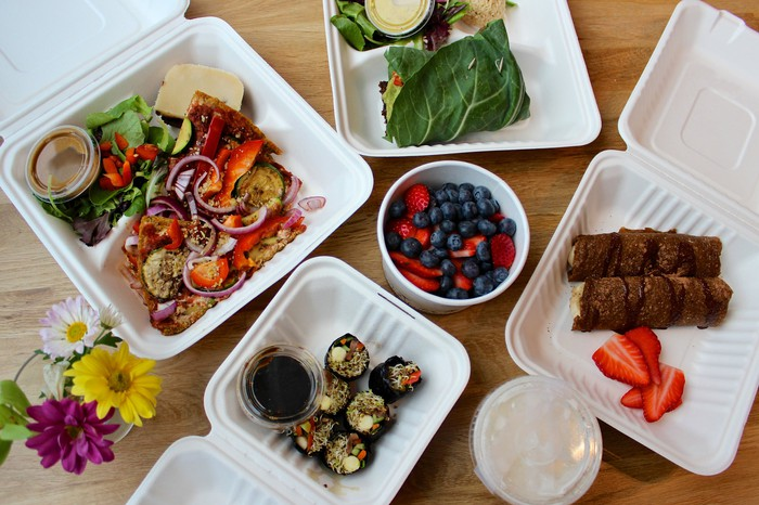 To-go, or delivery, boxes of fresh foods and fruits.