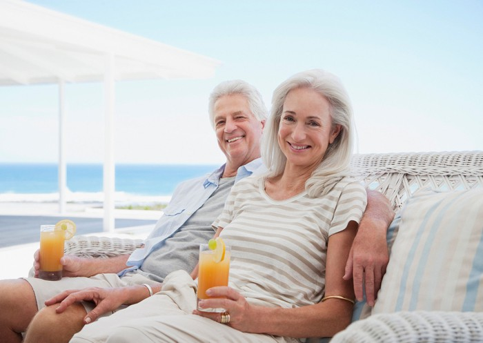 Senior couple holding cocktails outdoors