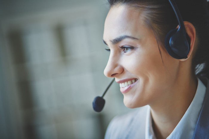 A woman smile while wearing a headset.