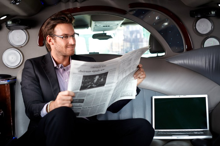 Man reading a newspaper in the backseat of a limo