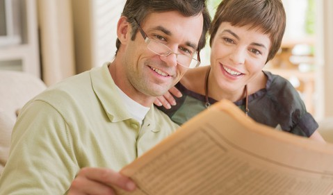 Couple Reading Financial Newspaper Getty