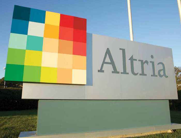 Sign with Altria name and multicolored logo, outside on a clear day.