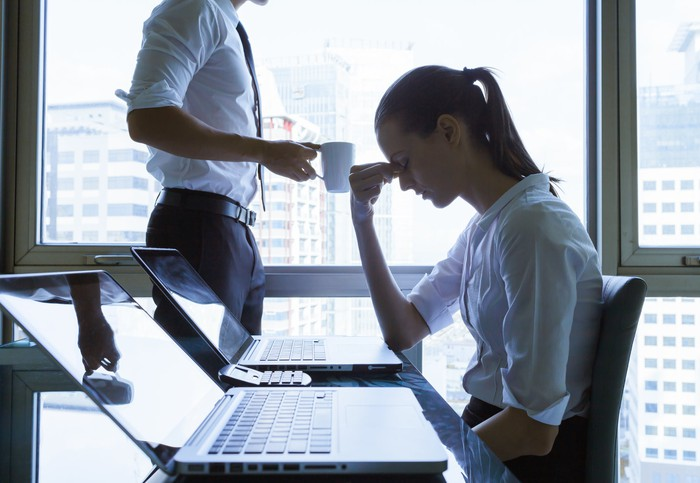Woman holding her head at a conference room table