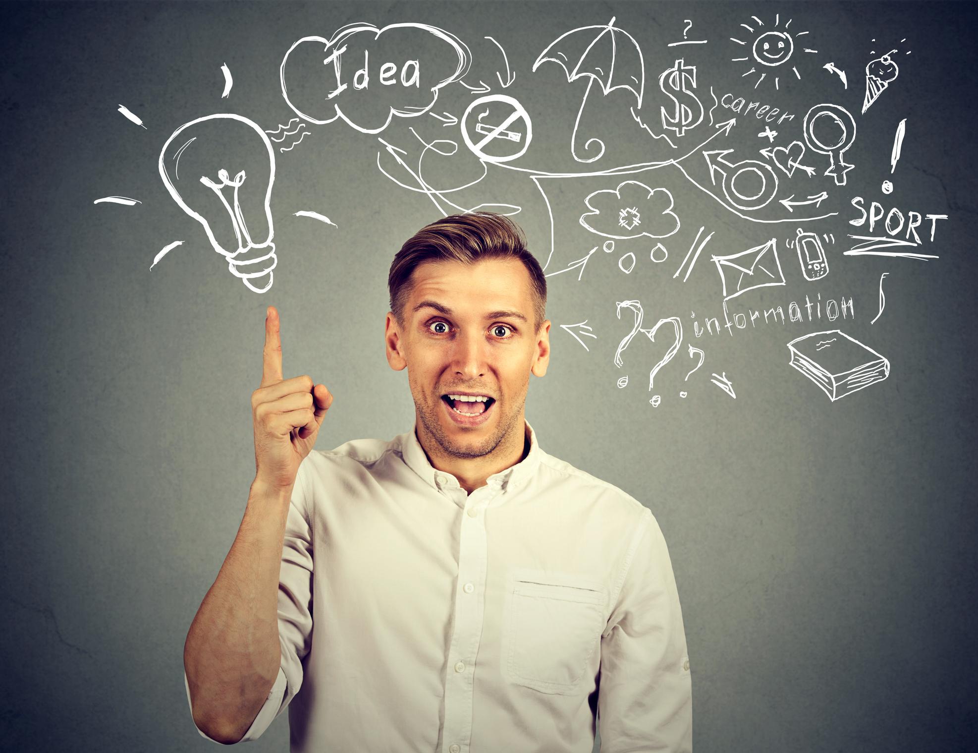 A man in a dress shirt points upward at a light bulb drawn on a blackboard.
