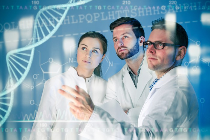 Scientists in lab coats collaborating in front of a monitor displaying a double helix.