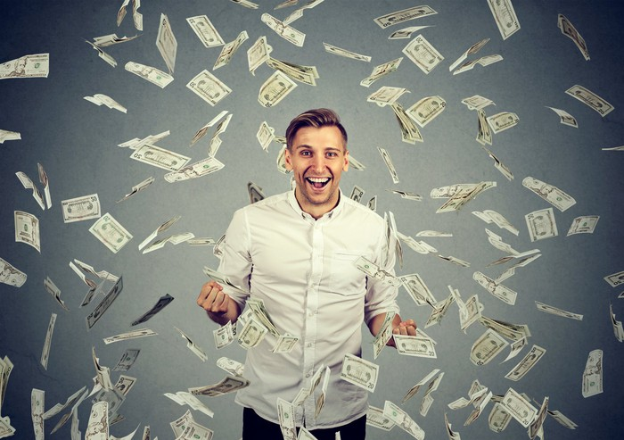 A young man in a dress shirt surrounded by falling paper currency.