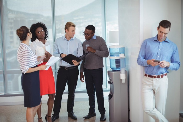 A group of colleagues standing around a water cooler.