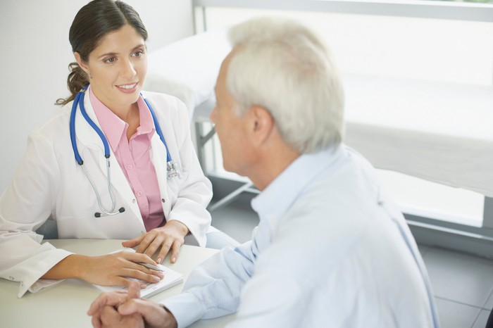 Female doctor talking to white-haired male patient