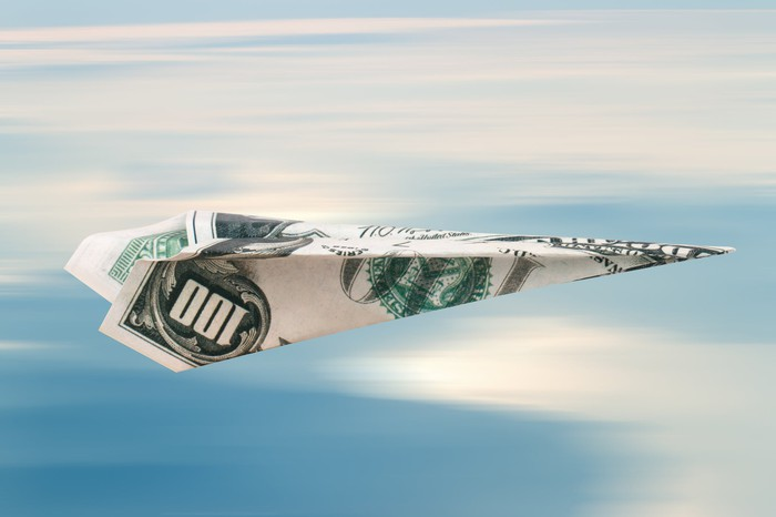 Paper plane folded from a hundred-dollar bill, on cloudy sky background.