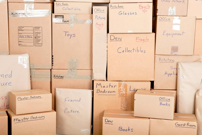 stacked moving boxes, labeled toys, housewares, etc.
