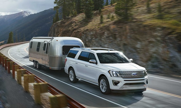 A white 2018 Ford Expedition, a full-size truck-based SUV, pulling an Airstream trailer on a mountain road.