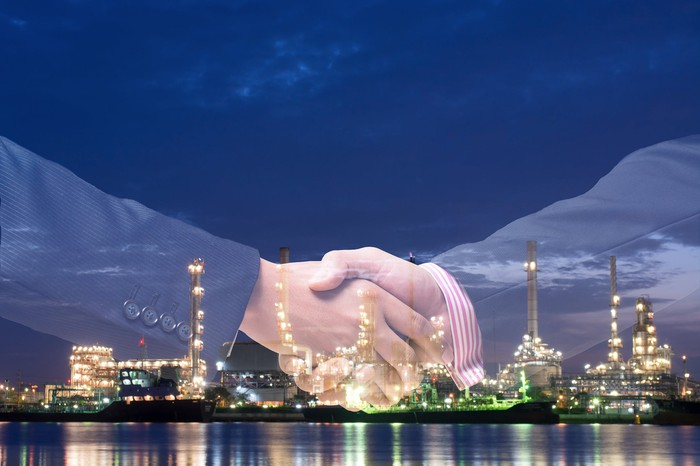 Double exposure of two hands shaking in front of an energy facility lit up at night