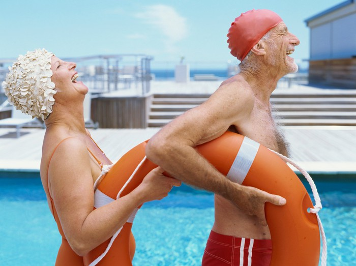 Two retirees in swimsuits holding a life preserver, laughing and smiling.