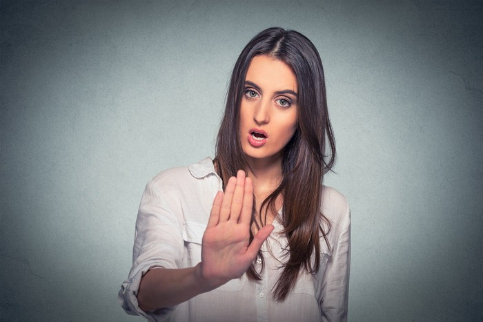 Woman holding out hand with serious look on her face.