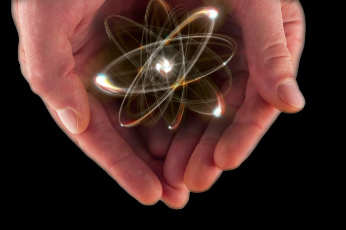 A cartoon of an atom in someone's cupped hands.