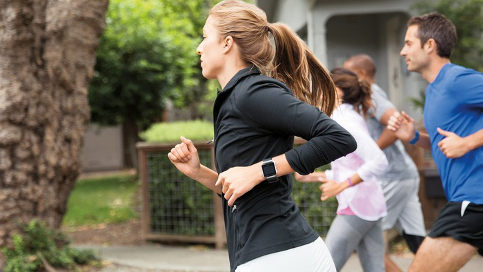 Woman running while wearing Fitbit device