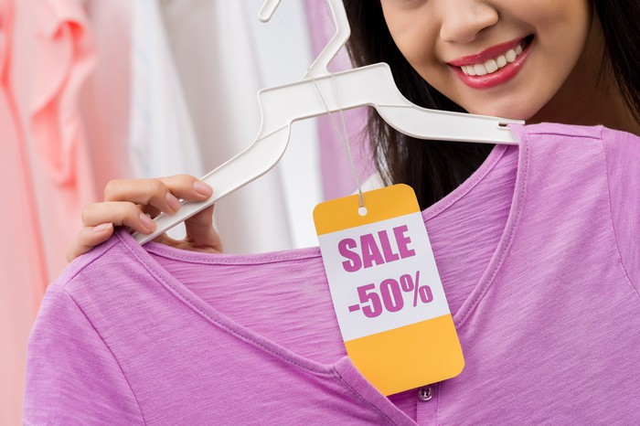 Woman holding shirt with 50 percent off sticker
