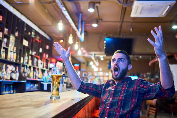A bearded man sitting in a bar with his hands raised and his mouth open in, perhaps, shock.