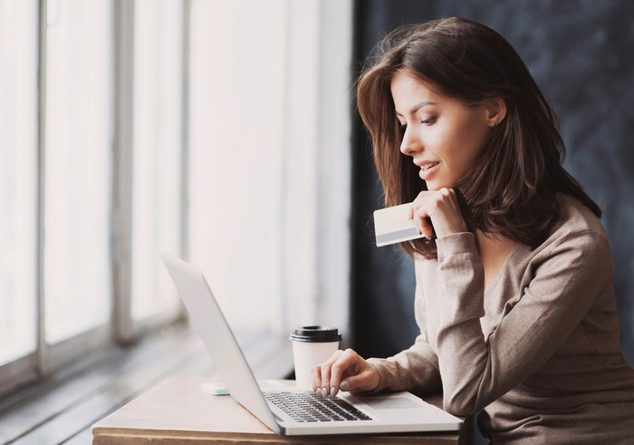 Woman sitting at table, using a computer and holding a credit card.