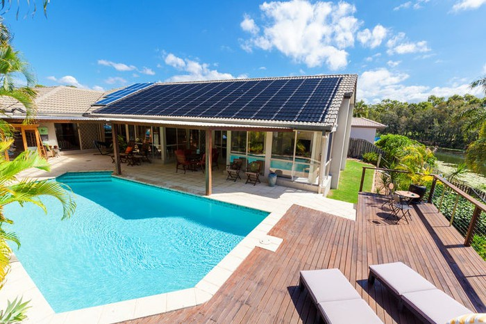 Solar panels on a roof of a house with an awesome pool.