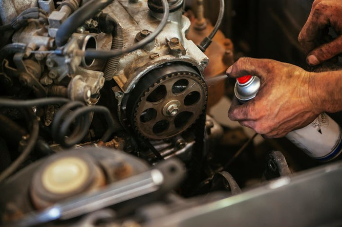 A mechanic spraying grease onto an engine.