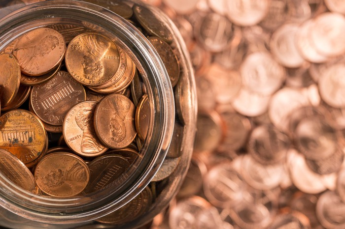 A jar of pennies surrounded by pennies.